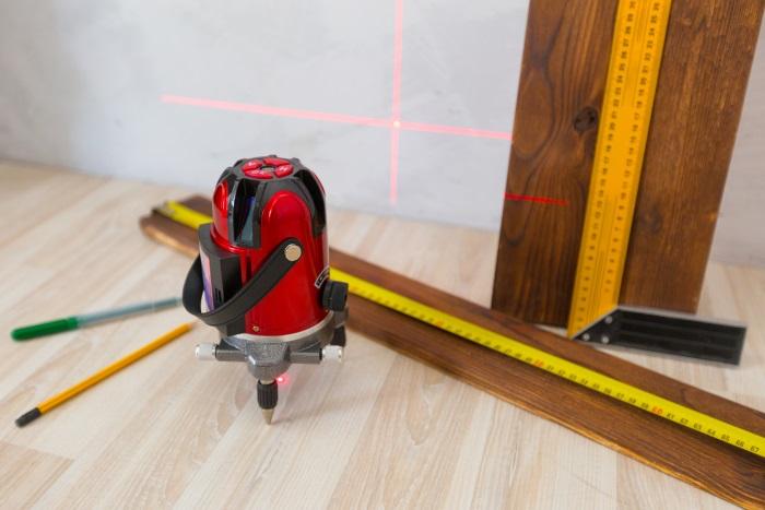 床や壁の傾きを確認する際に使われるレーザー測定器。一般の人ならビー玉を転がしたり、水を入れたペットボトル置くなどして簡易的なチェックができる