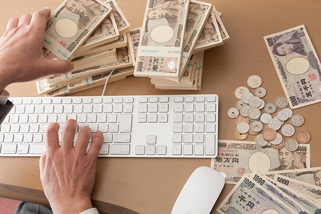 事務机とお金と男性