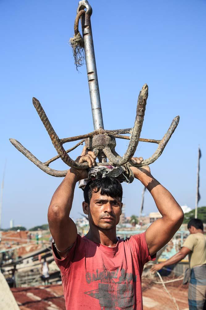 重い碇を頭に載せて運ぶ漁師 (C) Masashi Mitsui