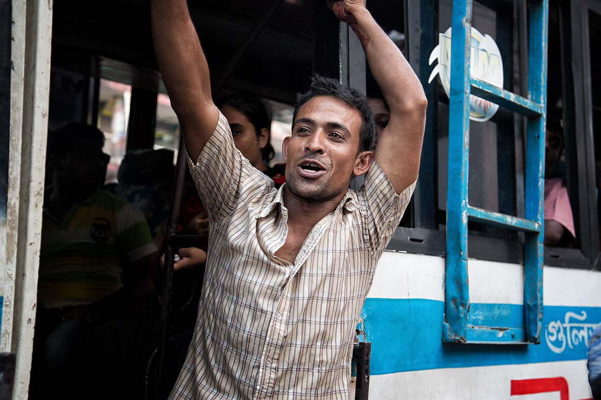 バスの呼び込みをする男。でかい声を張り上げ、車体をバンバン叩いて客を呼び込む (C) Masashi Mitsui