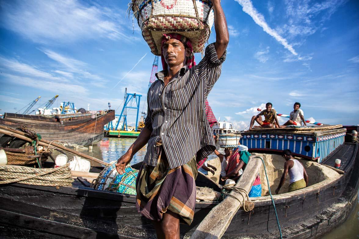 チッタゴンの船着き場で塩を運ぶ男。南部の塩田で作った塩を船で運び、チッタゴンにある工場で精製する (C) Masashi Mitsui