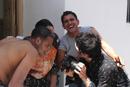 チュニジアの若者に写真を見せる小口さん