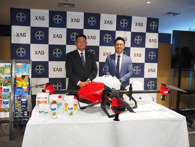 農薬散布用の新型ドローンを前に説明するXAGのジャスティン・ゴン共同創業者(右)と、バイエルクロップサイエンスの仁木理人氏