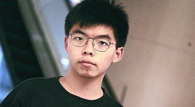 1280px-Joshua_Wong_holds_Honcques_Laus's_book