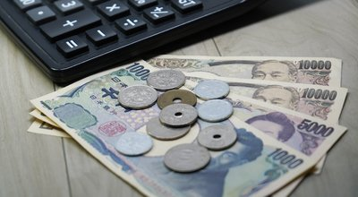 Japanese yen money banknotes and coins with calculator on the table, selective focus