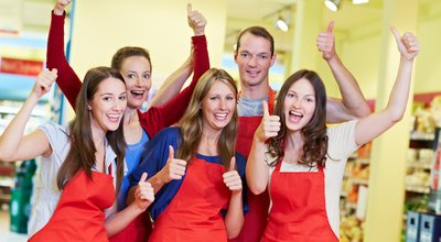 The winning team in the supermarket holds out the thumbs up, laughing