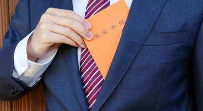 A man in a suit. An orange notebook with Japanese writing. Translation: Pension handbook.
