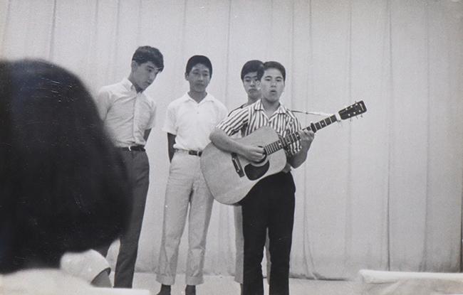 ギター片手に歌唱する玉川学園高校時代の滝沢(60年代後半頃)