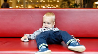 Child,Is,Lying,On,The,Couch,In,The,Shopping,Center