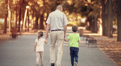 Grandfather,With,Two,Kids,Walking,In,The,Autumn,Park