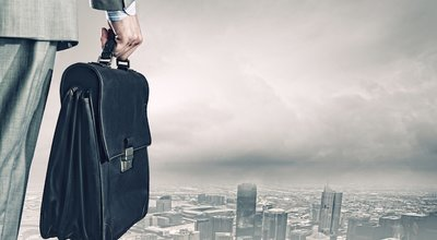 Back,View,Of,Businessman,With,Suitcase,Looking,At,City