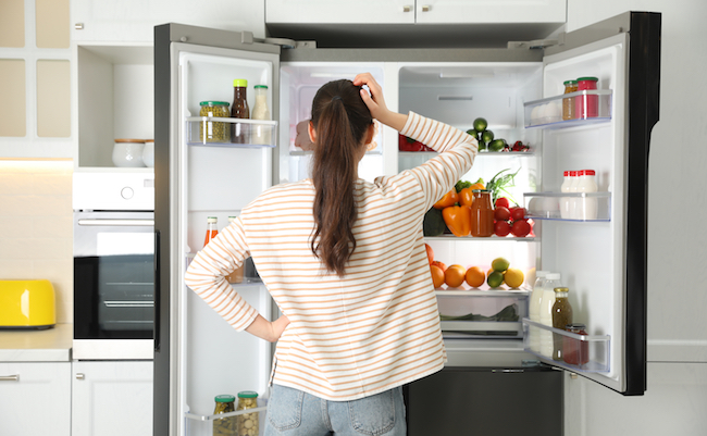 Young,Woman,Near,Open,Refrigerator,In,Kitchen,,Back,View