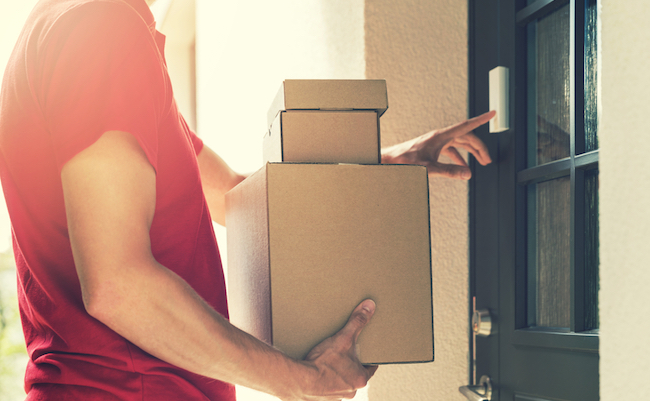 Delivery,Service,Courier,Ringing,The,House,Doorbell,With,Boxes,In