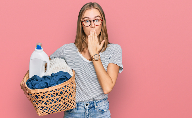 Beautiful blonde woman holding laundry basket and detergent bottle covering mouth with hand, shocked and afraid for mistake. surprised expression