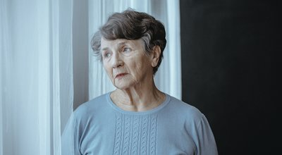 Worried,Grandmother,With,Alzheimer's,Disease,Isolated,Looking,Through,Window,In