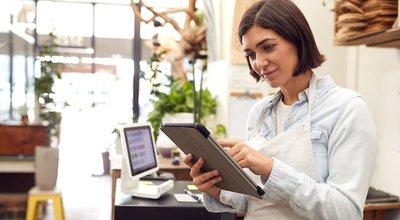 Female,Owner,With,Digital,Tablet,Standing,Behind,Sales,Desk,Of