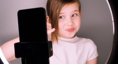 Small,Girl,Using,Camera,Of,Smartphone,In,Front,Of,Ring