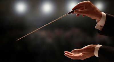 Conductor,Conducting,An,Orchestra,With,Audience,In,Background